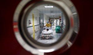 """Una sanitaria traslada a un paciente en la zona limpia de Covid del Hospital Gregorio Marañón de Madrid. En semanas, los sanitarios han pasado del drama a una """"calma tensa"""" que les pilla """"agotados"""", """"vacíos"""". Esperan ahora con cierto temor un posible rebr"""