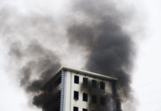 24075292 - fire burning and black smoke over the highrise building.