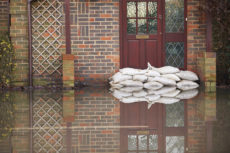 49640689 - sandbags outside front door of flooded house