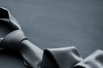 Grey man's business tie on dark background