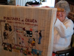 """Marjorie Ewbank holds up QUIP's """"Quaker Tapestry"""":http://www.Quaker-tapestry.co.uk panel, which should be finished by the end of the century."""