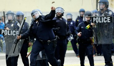 A police officer throws an object at protestors, Monday, April 27, 2015, following the funeral of Freddie Gray in Baltimore. Gray died from spinal injuries about a week after he was arrested and transported in a Baltimore Police Department van.