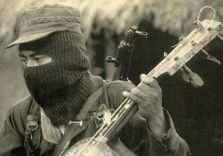 A black-masked Zapatista playing a three string Mexican bass guitar. Photo by Jose Villa