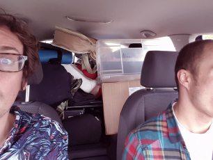 Der Dokumentarist (li.) und Bassist (re.) in einem der bis unters Dach beladenen Wagen.