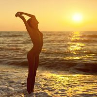 nude woman stretching in the waves during sunset