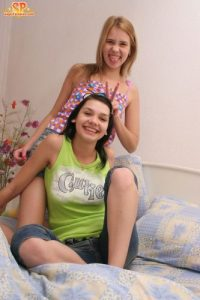 Young looking girls strip each other naked on their shared bed