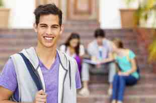 Portrait of confident student smiling with classmates sitting in background on college campus. Horizontal shot.
