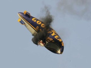 Helium-filled goodyear blimp catches fire and burns to destruction.