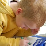 picture of young boy drawing an image on a piece of paper