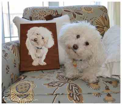 a dog next to a canvas painting of himself