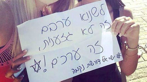 "Two Israeli Jewish girls with a sign in Hebrew that reads ""Hating Arabs is not racism, it's values"""