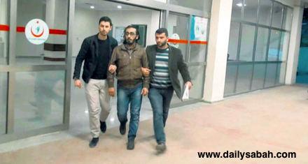 Two police officers escort Muhammad al-Rasheed following his arrest in Şanlıurfa in March