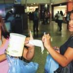 Unas mujeres muestran su dedo manchado de tinta como señal que ya hizo la cola y adquirió una lata de leche en polvo.