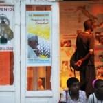 """Cubanos asisten a una """"exposición"""" de carteles que anuncian la """"visita"""" papal en Santiago de Cuba."""