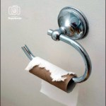 Toilet paper holder on white wall with an empty roll of paper