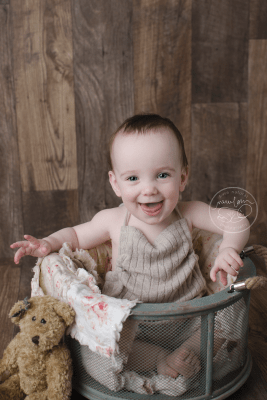 baby-photos-10-months-smiling-sitting-barnwood-floor-upcycled-sweater-sitter-romper-daddymackhats-rag-quilt-antique-teddy-bear-mesh-bucket