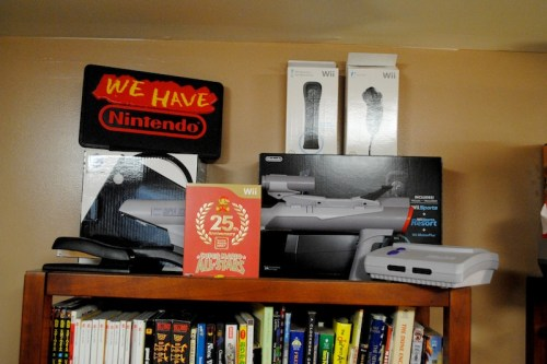 "The ""We have Nintendo"" sign in this picture was picked up from the now defunct 29'th Street Video in Pueblo Colorado when they shut down. We also picked up a Who Framed Roger Rabbit display, a massive Street Fighter II Champion Edition banner (easily 12 feet long and currently missing), a Genesis plaque, and a bunch of tattered movie posters. This store is actually where my parents bought our TurboGrafx-16s."