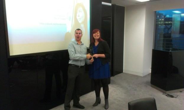 Dana Leeson of BSI receives a gold award from Sam Marshall