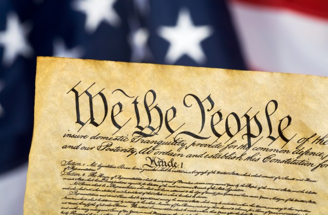 United States Constitution with Flag in background