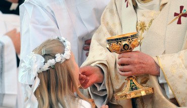 A girl kneels as she receives Communion from Pope Benedict XVI during a Mass celebrating the feast of Corpus Christi outside the Basilica of St. John Lateran in Rome May 22. The four dozen people who received Communion from Pope Benedict received the Eucharist on the tongue while kneeling. (CNS photo/Giancarlo Giuliani, Catholic Press Photo) (May 23, 2008) See POPE-KNEEL May 23, 2008.
