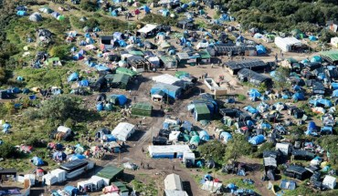 "An aerial picture taken  in Calais on October 9, 2015 shows a site dubbed the ""New Jungle"", where some 3,000 people have set up camp -- most seeking desperately to get to England, . The slum-like migrant camp sprung up after the closure of notorious Red Cross camp Sangatte in 2002, which had become overcrowded and prone to violent riots. However migrants and refugees have kept coming and the ""New Jungle"" has swelled along with the numbers of those making  often deadly attempts to smuggle themselves across the Channel.  AFP PHOTO / DENIS CHARLET"