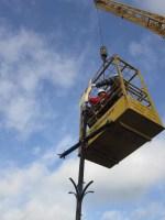 De stadsdeelvoorzitter plaatst de haan terug op het torenkruis.