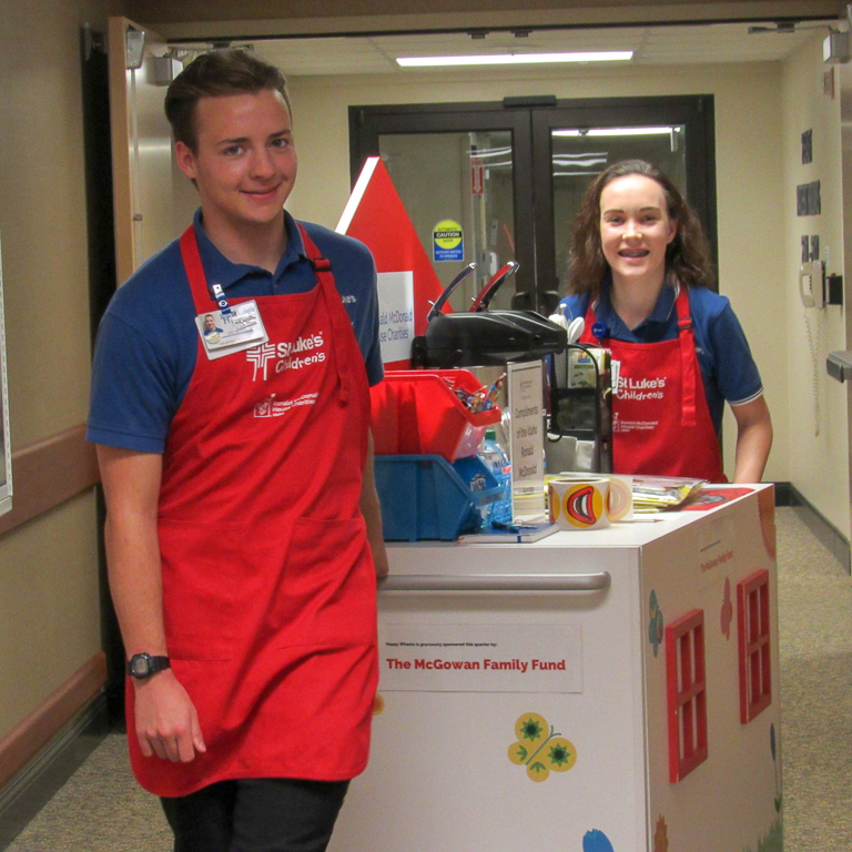 Leo and Jordankaty smile while volunteering for our Happy Wheels Hospitality Cart.