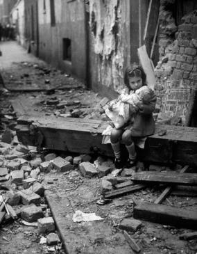 Little girl comforting her doll in the ruins of her  bomb damaged home, London, 1940