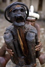 Dani tribesperson holding mummified remains of a Dani warrior
