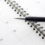 An open appointment book calendar and pen.