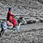A monk rides through the high desert of Ladakh's Himalayas