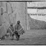 two boys dressed in Quechua clothing walk through Cusco