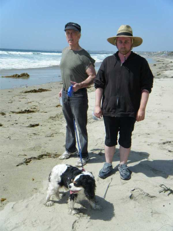 "Mike Cartel (l.), Ryan Short and Addy Rathbone (the Cavalier King Charles Spaniel) finish a grueling one-hour day at the beach shooting 68 shots where they made it up as they went along in Cinema Alley Cat style for ""Ghost Dog 2: Lady in the Ocean."""
