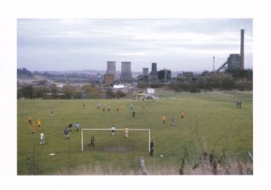A football pitch with cooling towers and chimneys in the background.