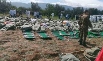 This image dated Wednesday, April 11, 2018, and posted by Algerian TV agency Ennahar TV, shows bodies gathered near scene of a fatal military plane crash at Boufarik military air base near the Algerian capital, Algiers. An Algerian military plane carrying soldiers and their families crashed soon after takeoff Wednesday into a field in northern Algeria, killing 257 people in what appeared to be the North African nation's worst-ever plane crash. (Ennahar TV via AP)