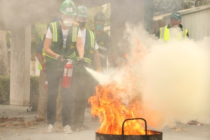CERT trainees practice extinguishing a controlled burn with Orange County Fire Authority firefighters during Saturday's session in San Juan Capistrano at the San Juan Mobile Estates. Photo: Eric Heinz