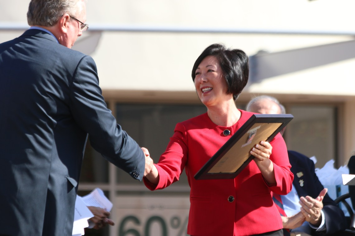Steve Craig (left) accepts a plaque from Orange County Supervisor Lisa Bartlett