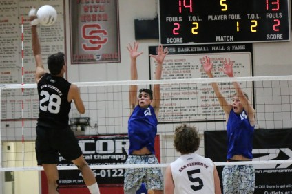 San Clemente senior Aaron Strange (28) hits against Dana Hills' Nathan Simpson (21) and Trevor Weinert (14) during a South Coast League game on March 29. Photo: Monica Merrill