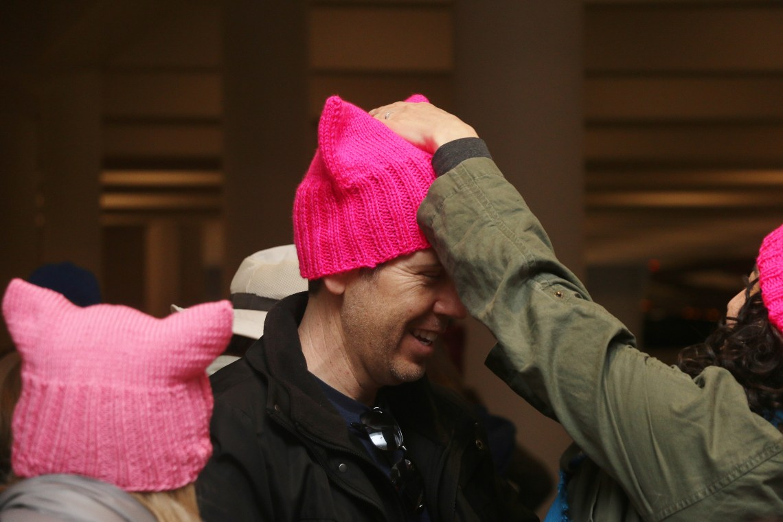 """David Gollom waits for the buses to Santa Ana while his wife, Stephanie Rothschild, places a pink hat on his head. The hats were made as a symbol of marchers' unity in Saturday's Women's March on Washington """"sister march."""" Photo: Eric Heinz"""