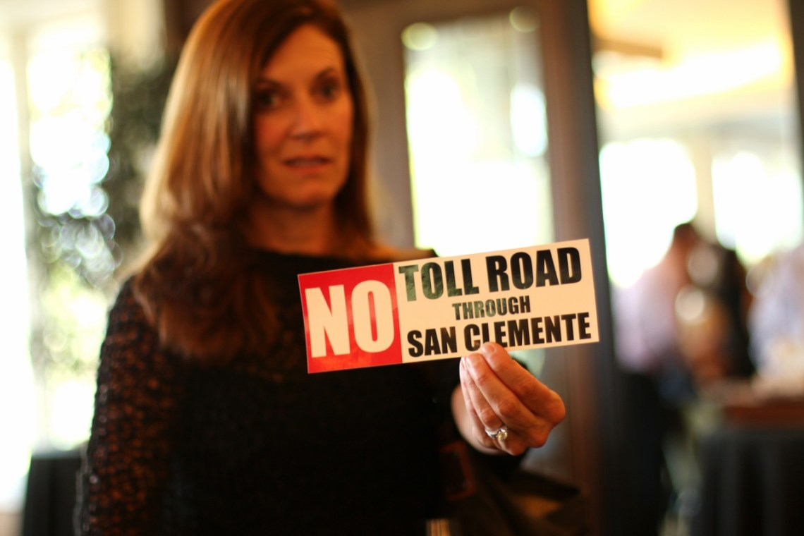 "Valerie Sweeney holds up a ""No Toll Roads Through San Clemente"" bumper sticker prior to the fundraiser for the Coalition to Save San Clemente meeting on Thursday, May 25, at Bella Collina San Clemente. Photo: Eric Heinz"