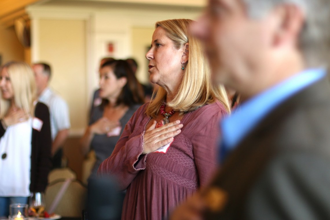 People recite the Pledge of Allegiance prior to the Coalition to Save San Clemente fundraiser on Thursday, May 25, at Bella Collina San Clemente. Photo: Eric Heinz