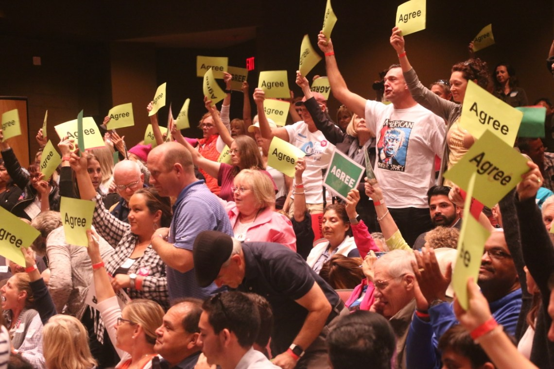 People held up green and red signs for whether they agreed or disagreed with Issa's views on certain issues. Photo: Eric Heinz