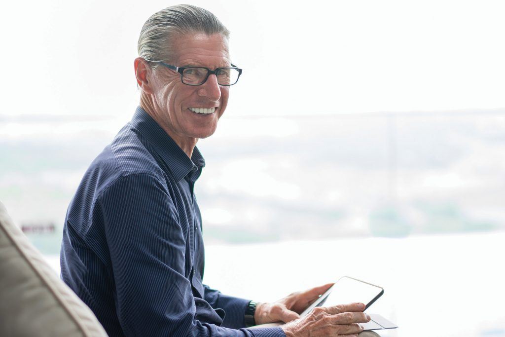 Portrait of happy senior man sitting on sofa, holding digital tablet, smiling at camera