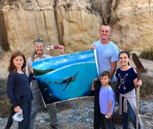Clockwise from far left: Trinity Noll, park ranger Cindy Marsh, Jed Noll, Taryn Medina, and Coda Noll hold up a painting hidden by Trevor Mezak that had been stuffed in a bluff for 10 years. Photo: Courtesy of the Noll family