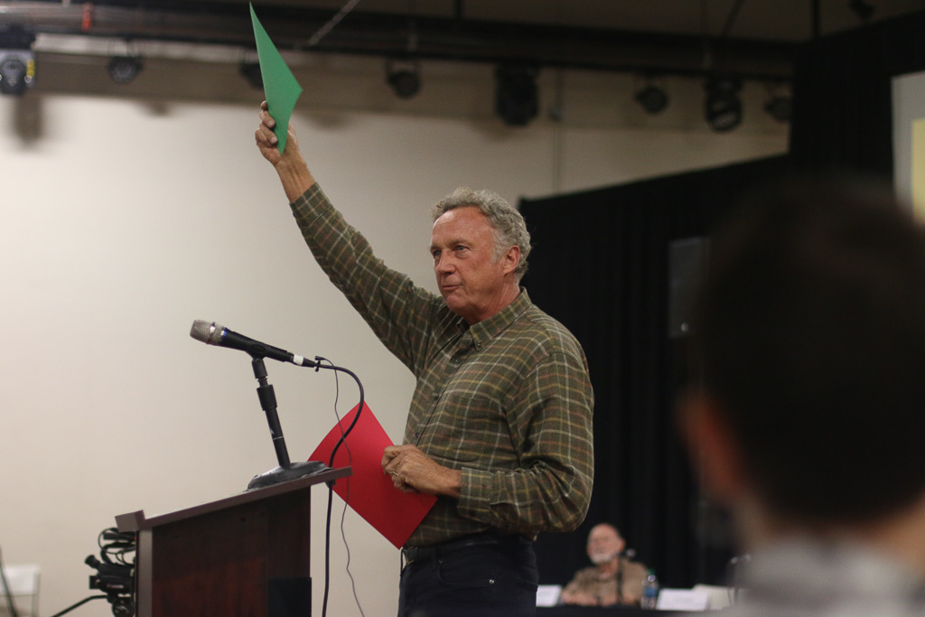 Gary Headrick, founder of environmental group San Clemente Green, holds up green and red cards for the audience to signify what they agree and disagree on with the CEP. Photo: Eric Heinz