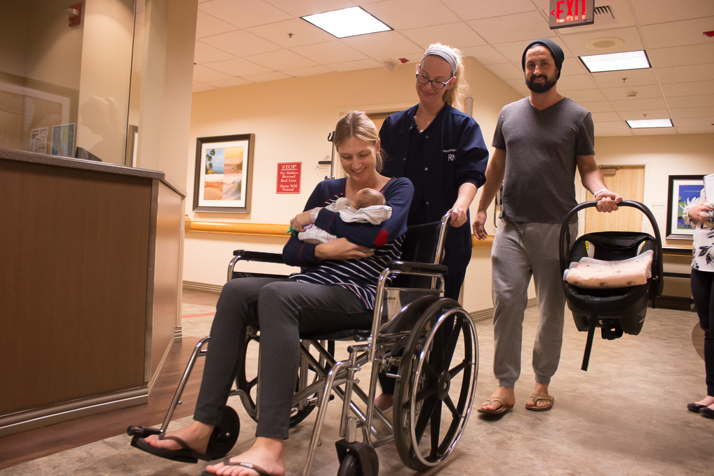 Megan Kroeger is wheeled out by a nurse and her husband and a nurse on Jan. 3 at MemorialCare Saddleback Medical Center in Laguna Hills. Photo: Eric Heinz