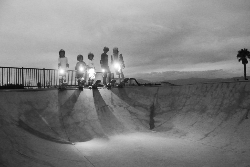 A group of young skateboarders gathers at dusk at the Ralphs Skate Court in San Clemente. Photo: Eric Heinz