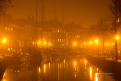 Old ships in a canal in Groningen, Holland, during a foggy, autumn night.