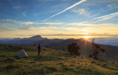 Hiker enjoying the summer sunrise while camping in the mountains.