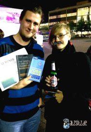 Nikolai Eberlein und Luise Schitteck in guter Laune auf dem #vsp14. Luise mit Papierschnurrbart und Bier, Nikolai mit Büchern und Zeitung.